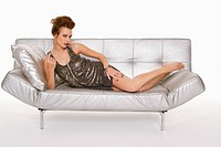 Young woman in formalwear lying on sofa