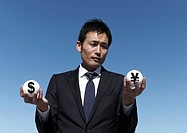 Businessman holding currency sign balls in his hands