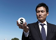 Businessman holding dollar sign ball