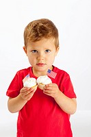 A Young Boy Holds Two Cupcakes With American Flags In Them