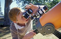 boy looking through camera attached to telescope