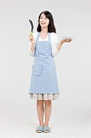 Young woman in apron holding dining utensil