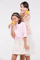 Mother and daughter holding oranges