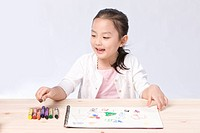 Girl coloring with crayons at desk