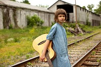 Girl with guitar standing near railroad tracks.