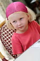 Stock photo of a four year old girl waiting at a restaurant table