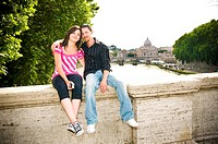 Portrait of young couple sitting on ledge with Saint Peter&#8217;s Basilica behind, Rome, Italy