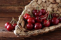 Cherries Prunus in a wicker basket on rustic wood