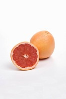 Whole and halved pink grapefruit on white background