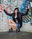 Young woman with dark hair wearing hot pants, a black leather jacket and high heels posing in front of a wall with graffiti