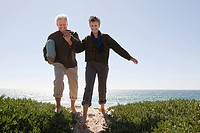 Mature couple walking over dune