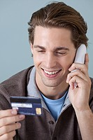 Young man on the phone with credit card