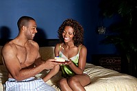 Young couple in bedroom with birthday cake