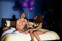 Young couple in bedroom with balloons
