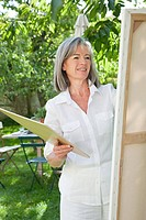 Mature woman painting at easel