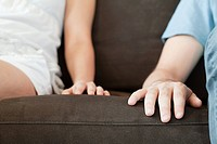 Close up of hands of couple on sofa