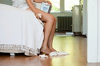 Legs of woman on bed with tissues on floor