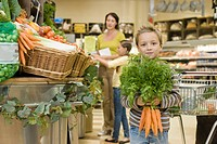 Boy in supermarket with bunch of carrots