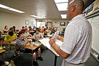 Using a check list, a Southern California high school teacher checks attendance at the beginning of a class period