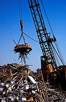 A giant crane-mounted electromagnet is used to move a pile of iron and steel items at a scrap yard in Carson, California