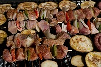 Grill meat and vegetabels on skewers on a barbecue grid