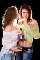 Portrait of the two girlfriends with a cognac bottle