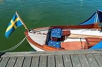 White Wooden Boat docked with the Swedish flag