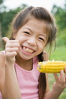 Girl eating corn, Chiba Prefecture, Honshu, Japan