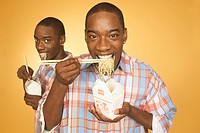Twin teen boys eating noodles from cartons.