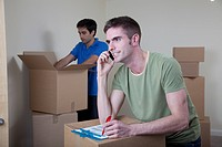 Two men unpacking boxes in apartment