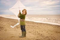 Young boy on beach holding kite. Fall