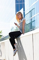 Women sitting on wall with ipod