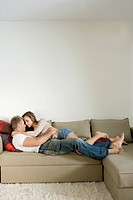 Young couple lying on sofa and embracing