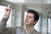 USA, New Jersey, Jersey City, Businessman writing calculations on glass