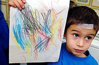 A child holding up his drawing