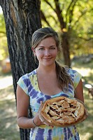 USA, Colorado, Cheerful young woman holding pie