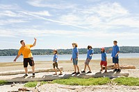 Male camp counselor with children at beach