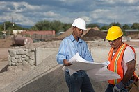Two construction workers discussing blueprints on building site