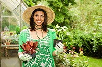 Woman holding plants in garden
