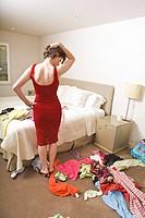 Woman in bedroom choosing outfit