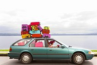 Woman and dog driving car stacked with colorful suitcases
