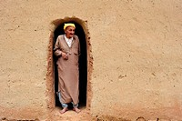 Elderly Berber man wearing a turban looking out of the entrance of his mud house, High Atlas Mountains, Morocco, Africa