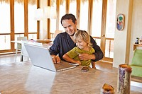 man working on laptop with child on lap