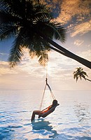 Maldive Islands. Woman in hammock under palm tree at sunrise