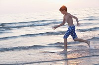 Boy skim boarding in the lake at sunset