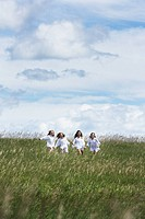 girls holding hands running through fields