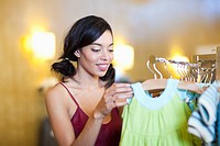 Mixed race woman looking at children's clothing in store