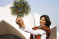 Mixed race woman holding peacock feather fan