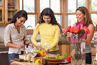 Hispanic friends drinking wine and cooking
