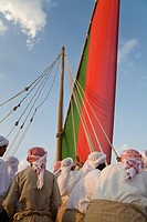 UAE, Dubai. Men in traditional clothes raising a dhow sail during National Day celebrations. Credit: Bill Young / Jaynes Gallery / DanitaDelimont.com